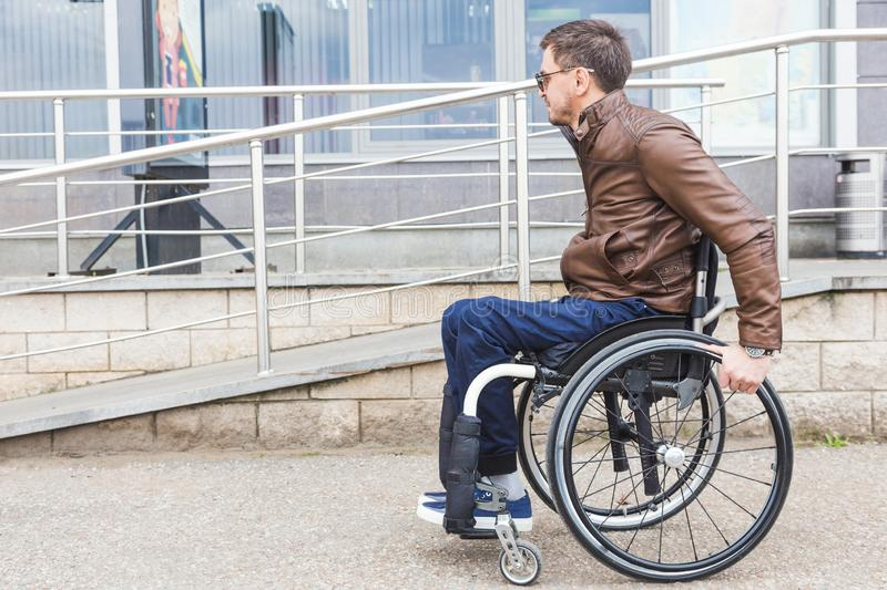 Man in a wheelchair use a wheelchair ramp. royalty free stock photography