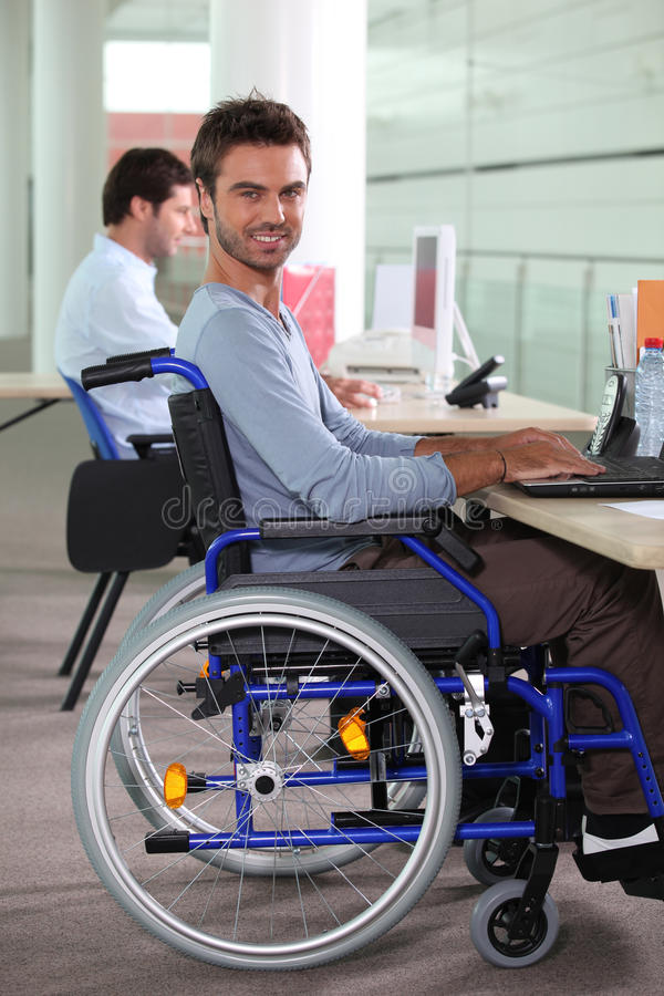 Man in a wheelchair using a computer royalty free stock images