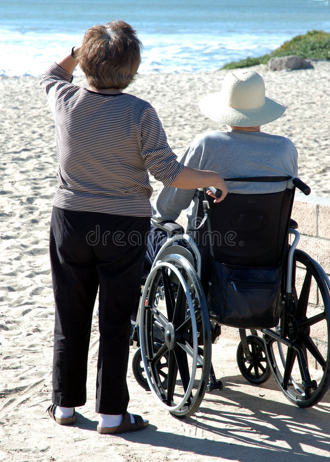 Man in wheelcheair at the beach stock images