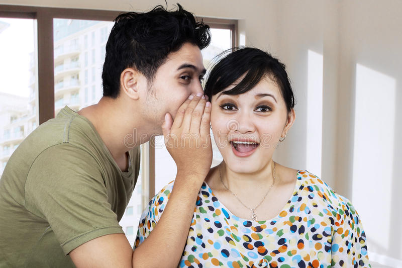 A man whispering a secret to his girlfriend royalty free stock photo
