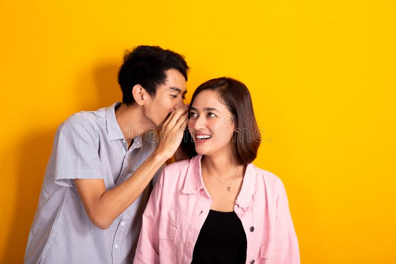 Woman looked shocked while man whispering to his ear. Man whispering to a women about gossip, women looked shocked shoot over yellow background royalty free stock image