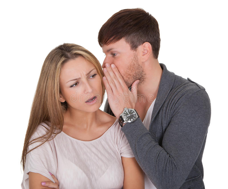 Man whispering in a woman's ear royalty free stock image