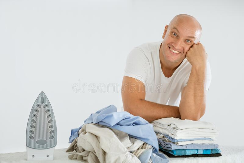 A man on a white background with an Ironing Board, there is an iron and there are ironed things and not ironed.  royalty free stock photo