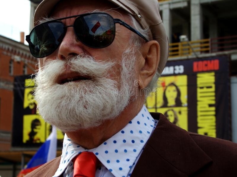 Man with a white beard wearing sunglasses and a hat. Street stock image