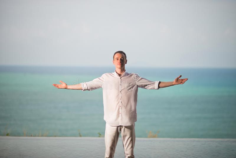 Man in the white clothes standing on a background of ocean with divorced hands to the side, enjoying the freedom. The man in the white clothes standing on a stock photos