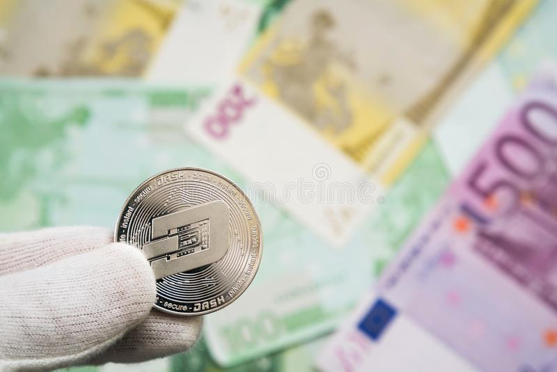 Man in white cloves holding Dash coin between fingers with Euro bank notes in the background. Digital currency, block chain market stock image