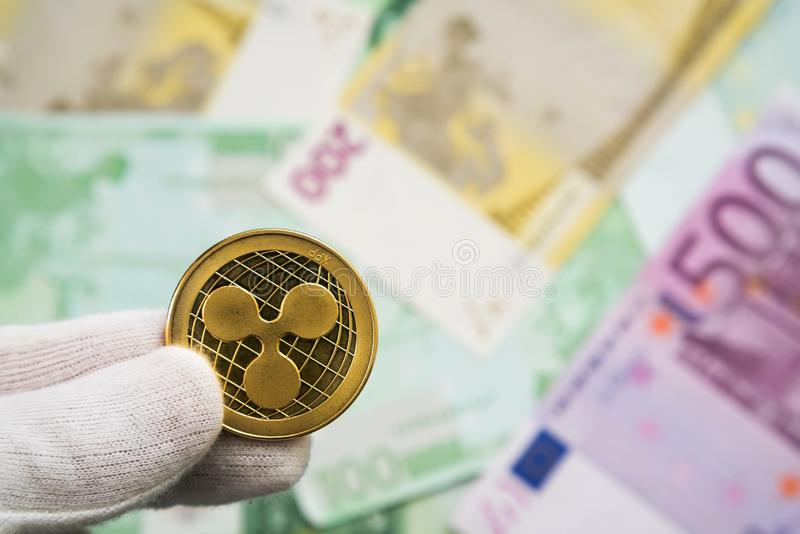 Man in white cloves holding Ripple coin between fingers with Euro bank notes in the background. Digital currency, block chain stock photo