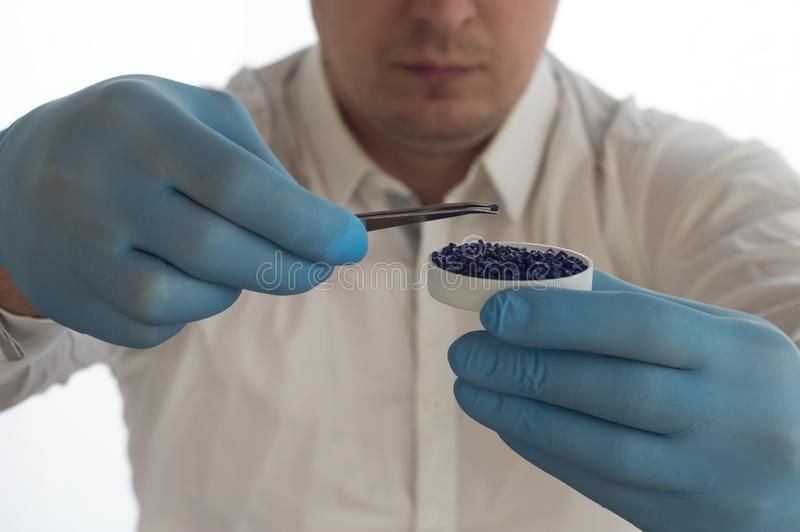 A man in a white coat holding tweezers and plastic pellets and granules in the laboratory royalty free stock photography