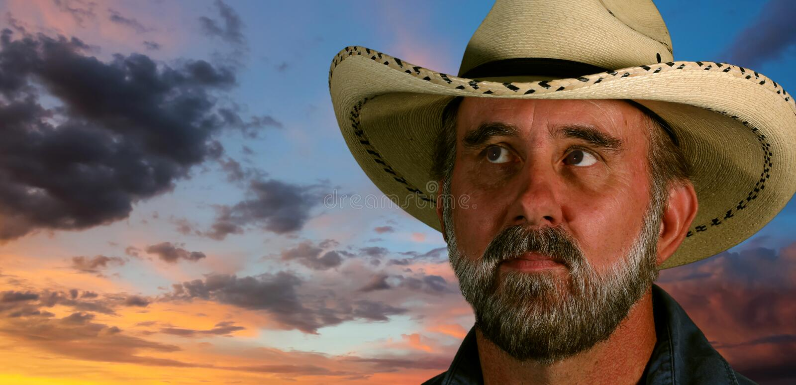 A Man in a White Cowboy Hat at Sunset. A Man with Brown Eyes and a Gray Beard in a White Straw Cowboy Hat at Sunset stock image