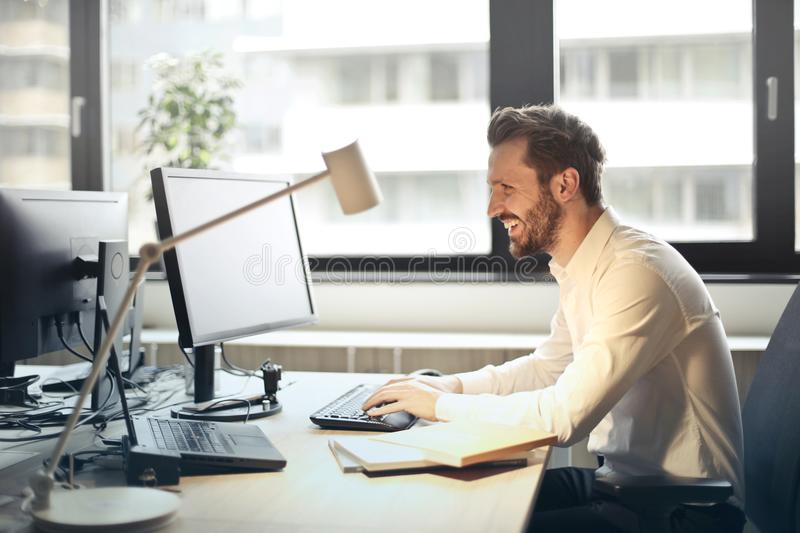 Man in White Dress Shirt Sitting on Black Rolling Chair While Facing Black Computer Set and Smiling stock photos