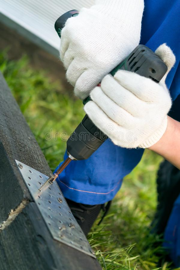 A man in white gloves spins a screw into a black wooden beam with an electric screwdriver royalty free stock photography
