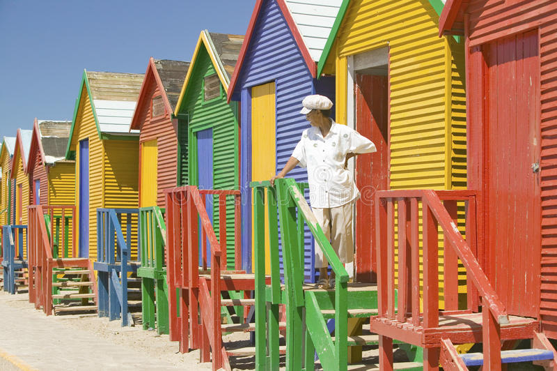 Man with white hat standing in front of bright Crayon-Colored Beach Huts at St James, False Bay on Indian Ocean, outside of Cape royalty free stock photo