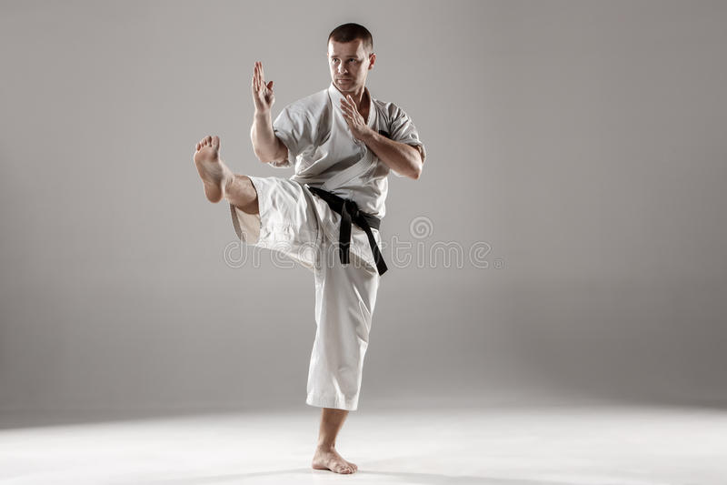 Man in white kimono training karate. Man in white kimono and black belt training karate over gray background stock image