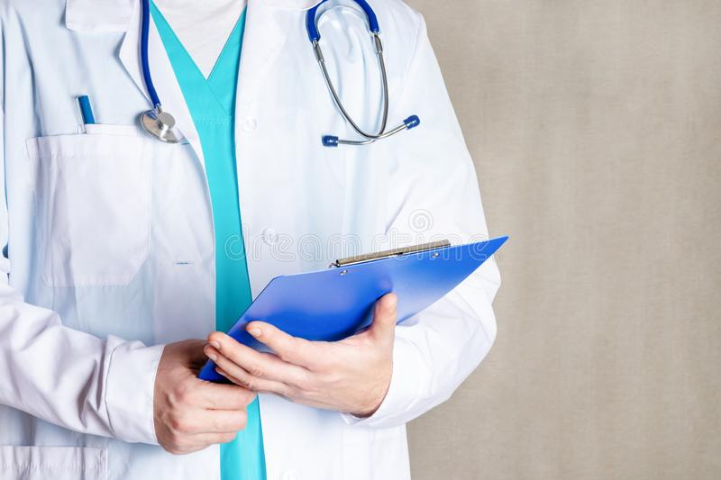 A man in a white medical gown is holding a blue folder. Cropped photo of a doctor, closeup. Bright photo. royalty free stock image