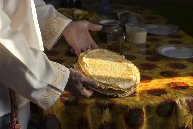 A man in a white national Slavic costume holds a plate of pancakes in his hand. Russian national food. Maslenitsa. Shrovetide.  royalty free stock images