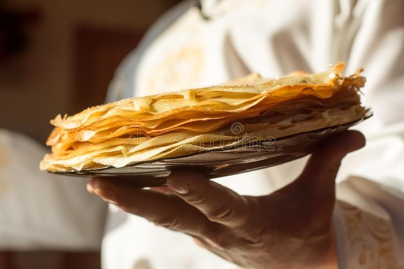 A man in a white national Slavic costume holds a plate of pancakes in his hand. Russian national food. Maslenitsa. Shrovetide. A man in a white national Slaviose stock photos
