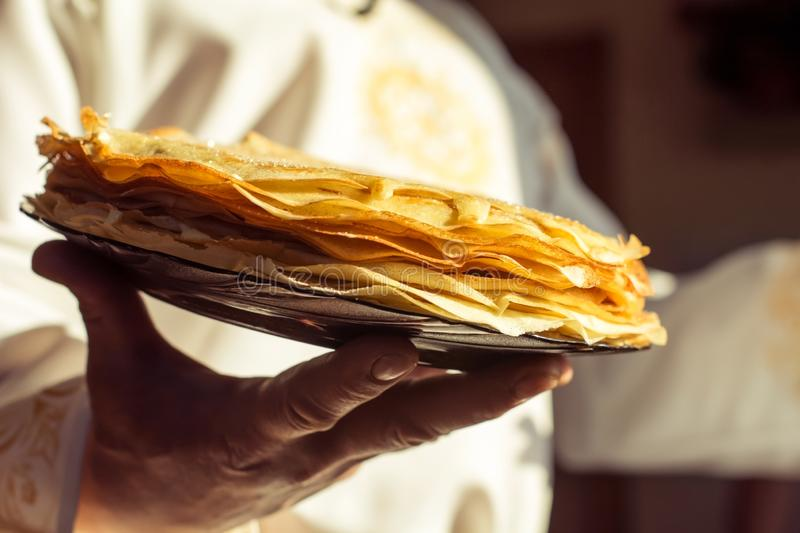 A man in a white national Slavic costume holds a plate of pancakes in his hand. Russian national food. Maslenitsa. Shrovetide. A man in a white national Slaviose stock image