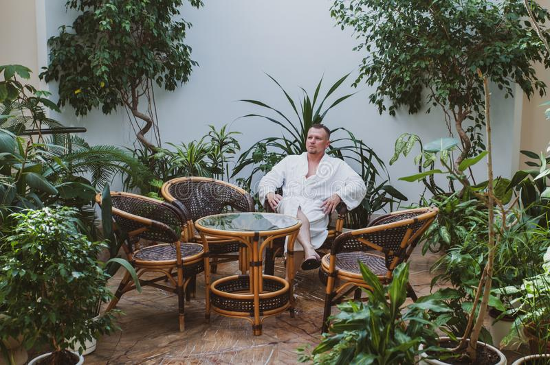 Man in a white robe is resting in a spa center surrounded by plants stock image