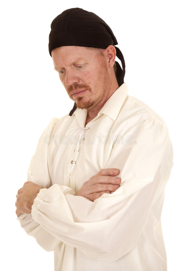 Man white shirt black bandana arms folded look down. A man in a white shirt and a black bandana looking down royalty free stock photos