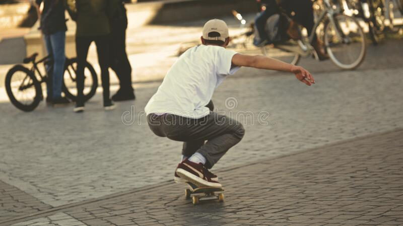 Man In White Shirt And Brown Jeans Riding Skateboard Free Public Domain Cc0 Image