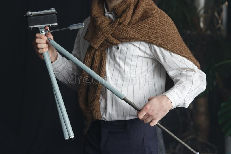 a man in a white shirt and a brown sweater is holding an old tripod with a camera, a vintage royalty free stock image