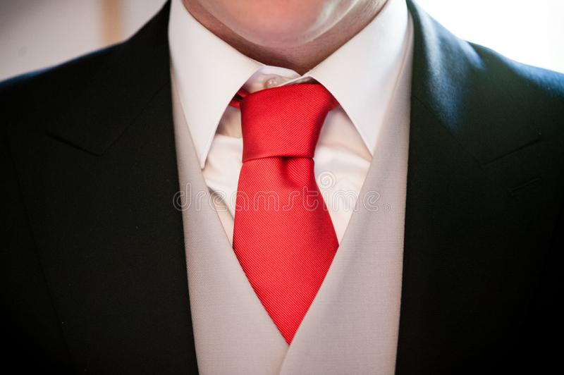 Man with white shirt, grey vest, black jacket and red tie stock images