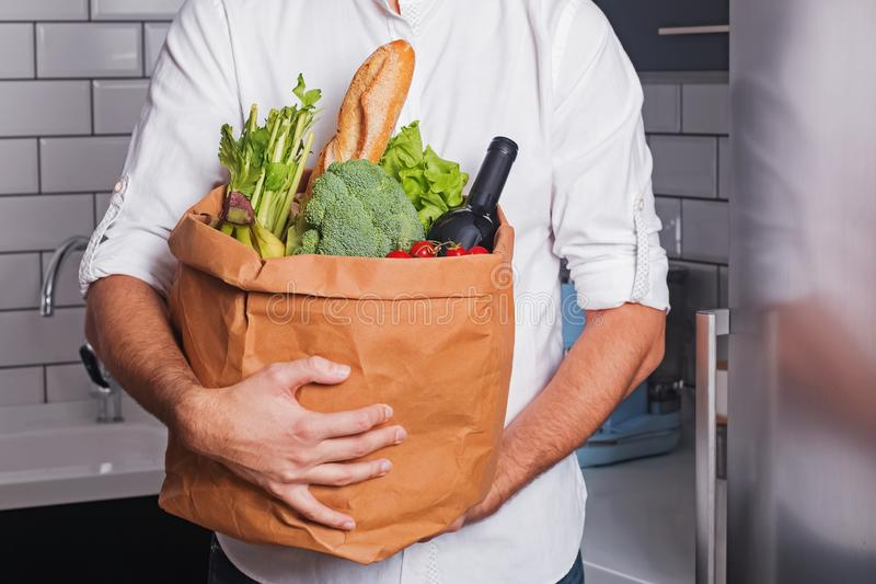 Man in white shirt holding a reusable bag full of fresh products from grocery store or supermarket royalty free stock image