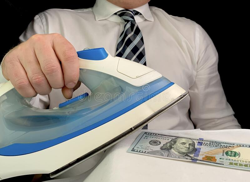 A man in a white shirt holds an iron in his hand. A man smoothes dollars with an iron. Concept: dirty money. A man in a white shirt holds an iron in his hand. A stock image