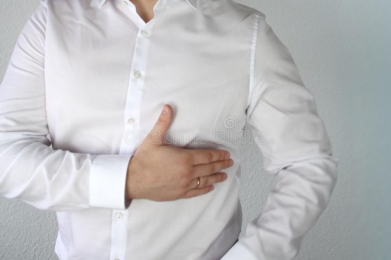 Man in a white shirt holds on to the chest in the heart, symbol of problems, pain, illness, first aid, close-up stock photos