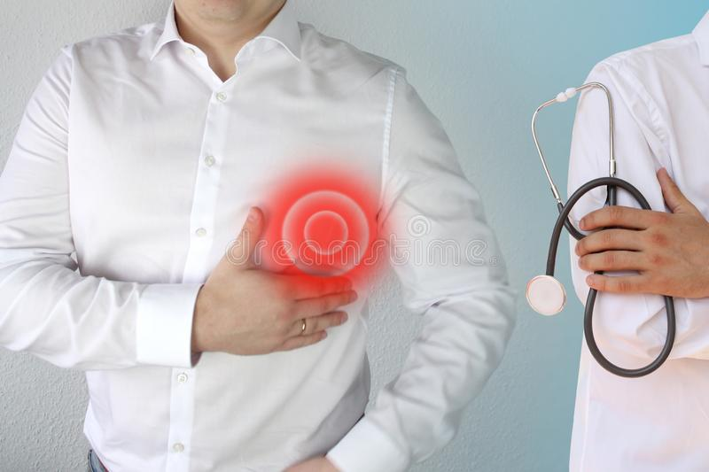 Man in a white shirt holds on to his chest in the heart area, a red circle, a symbol of throbbing pain, a doctor is standing next royalty free stock image