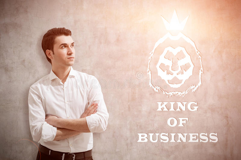 Man in white shirt and king of business sketch, toned. Young man in white shirt standing near concrete wall with king of business sketch on it. Concept of true stock images