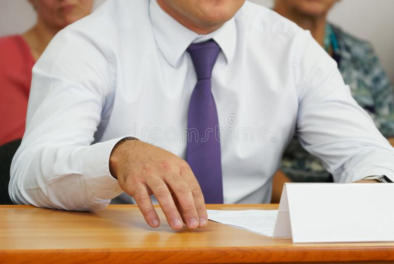 A man in a white shirt and a lilac tie gestures during a speech. Participant in the meeting and discussion. Shallow depth of field stock photo