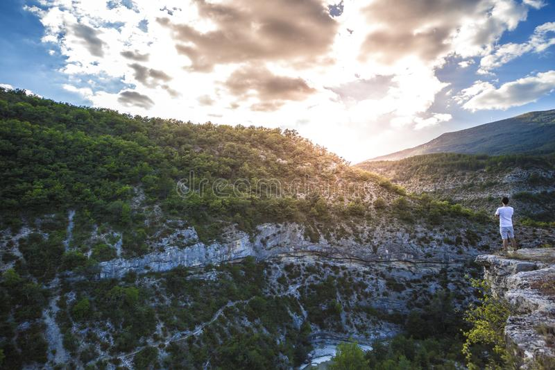 Man in White Shirt Standing on Top of Mountain Cliff Under Cumulus Clouds stock images