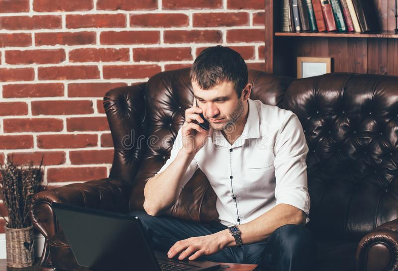 A man in white shirt talks on the phone. Businessman sits on a leather sofa behind his laptop on the background of a shelf with stock photography