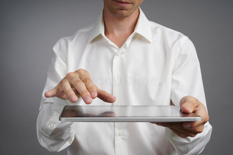 Man in the white shirt works with tablet PC. Hands closeup shot stock image