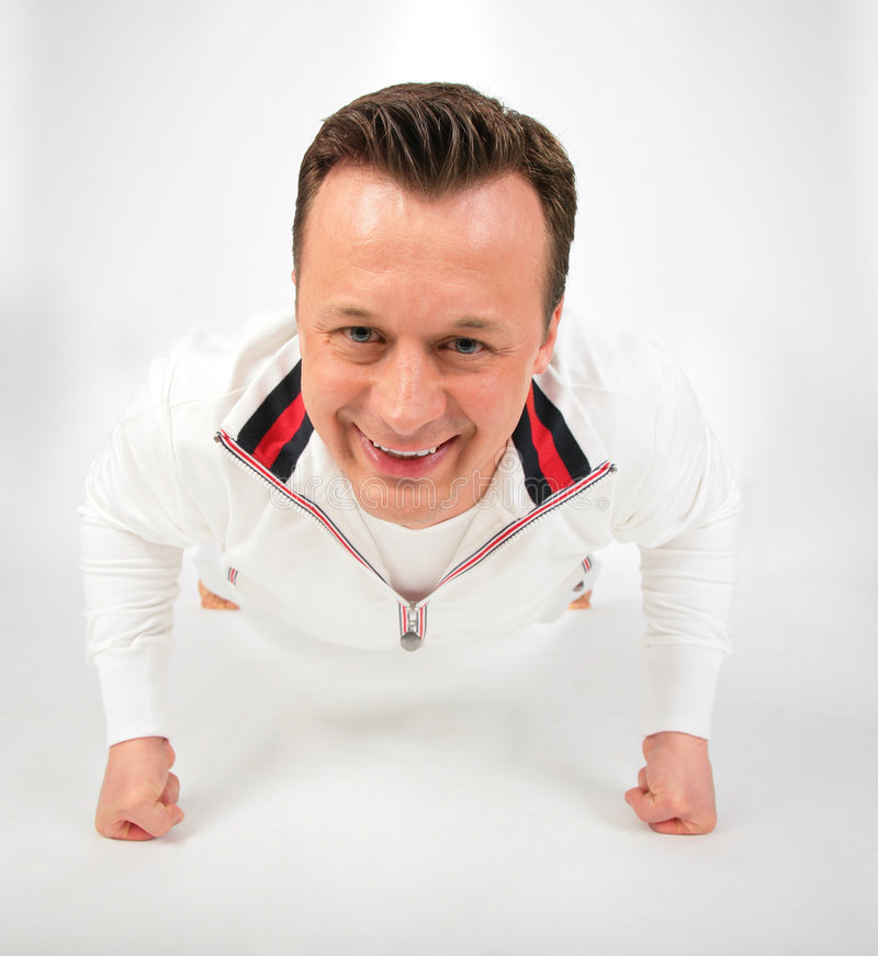 Man In White Sports Suit Does Exercise Royalty Free Stock Image