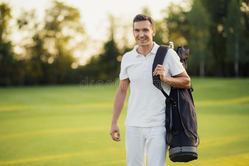 A man in a white suit walks around the golf course with a golf club bag and smiles stock photos