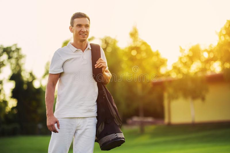 A man in a white suit walks the golf course with a bag of golf clubs against a beautiful sunset stock image