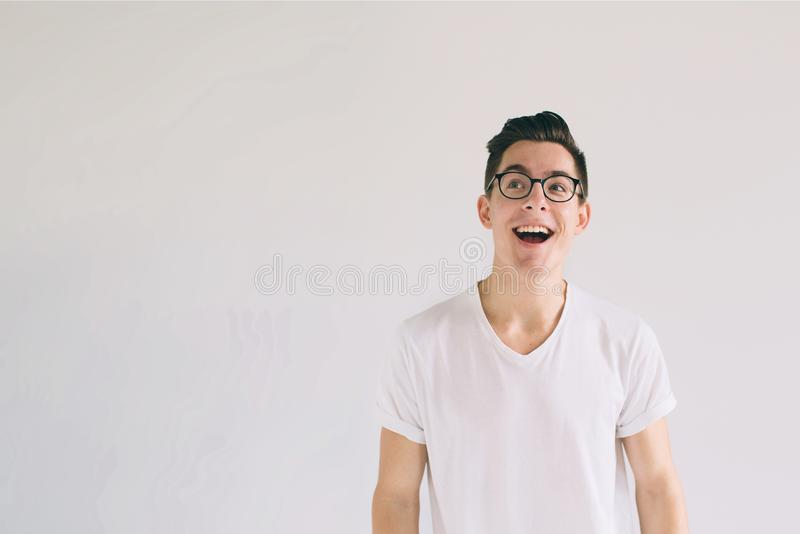 Man in white t-shirt and glasses with big smile isolated on white background. A very kind student has a good mood stock image