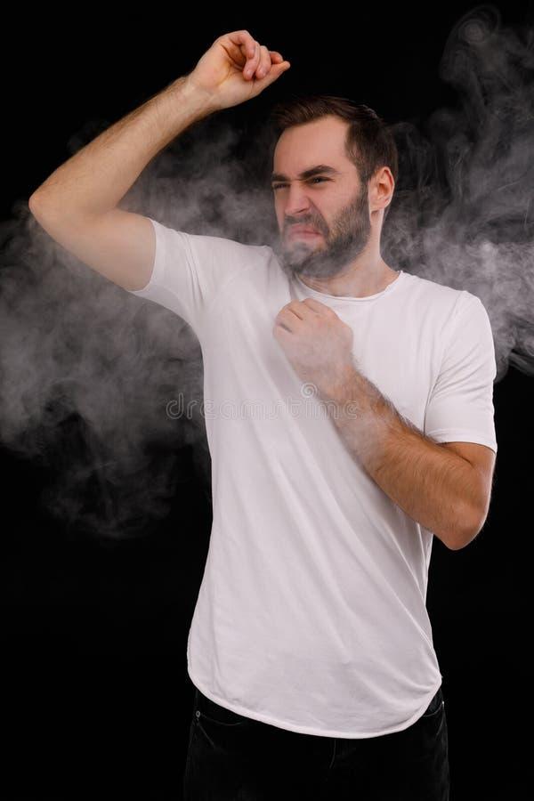 Man in white t shirt hates cigarette smoke stock photos