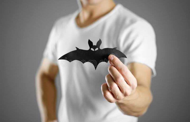 A man in a white t-shirt holds a black silhouette of a bat. Close up royalty free stock photography