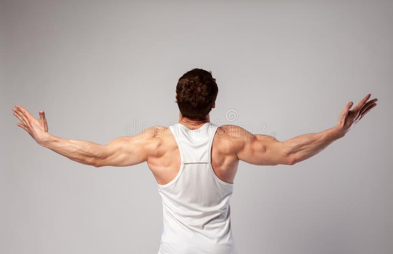 A man with a muscular body spread his arms to the side and looks up royalty free stock image