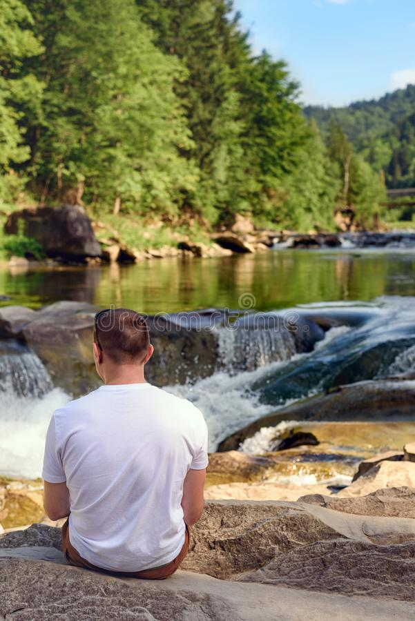 Man in white t-shirt sitting on the bank of the river against the background of a waterfall and green forest. Sunny day. Back view.  royalty free stock image