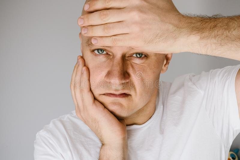 Man in white t-shirt suffers from toothache. royalty free stock image
