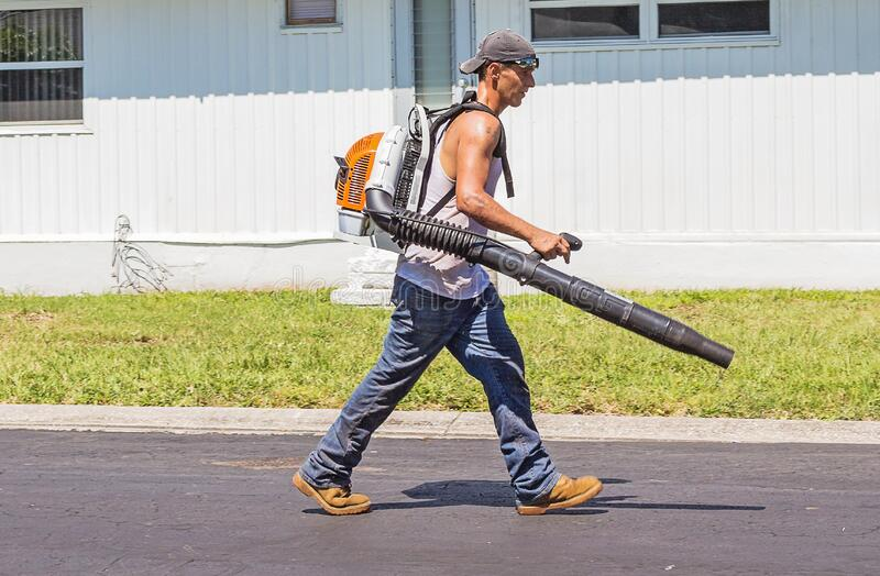 Man in White Tank Top and Blue Denim Pants With Leaf Blower Outdoors during Daytime royalty free stock photos