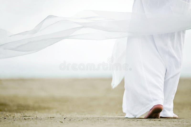 Man in white walking on sand stock image