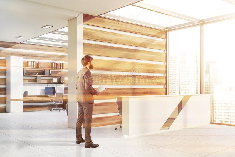 Man in white and wooden office with reception stock photography