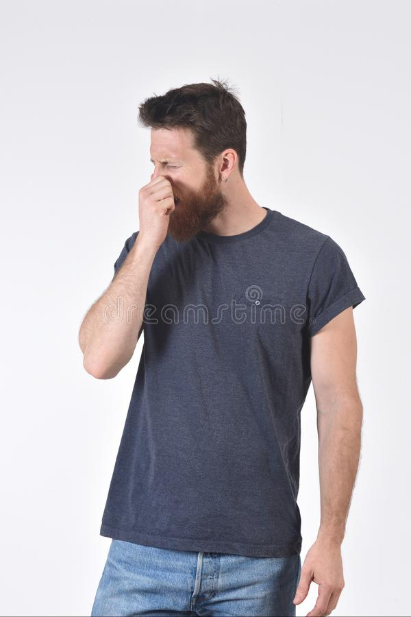 Man who covers his nose with his fingers because it makes an smell bad.  royalty free stock photos
