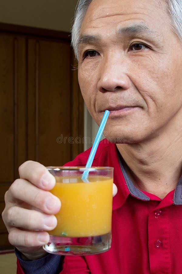 Man who drinking Orange juice stock photography