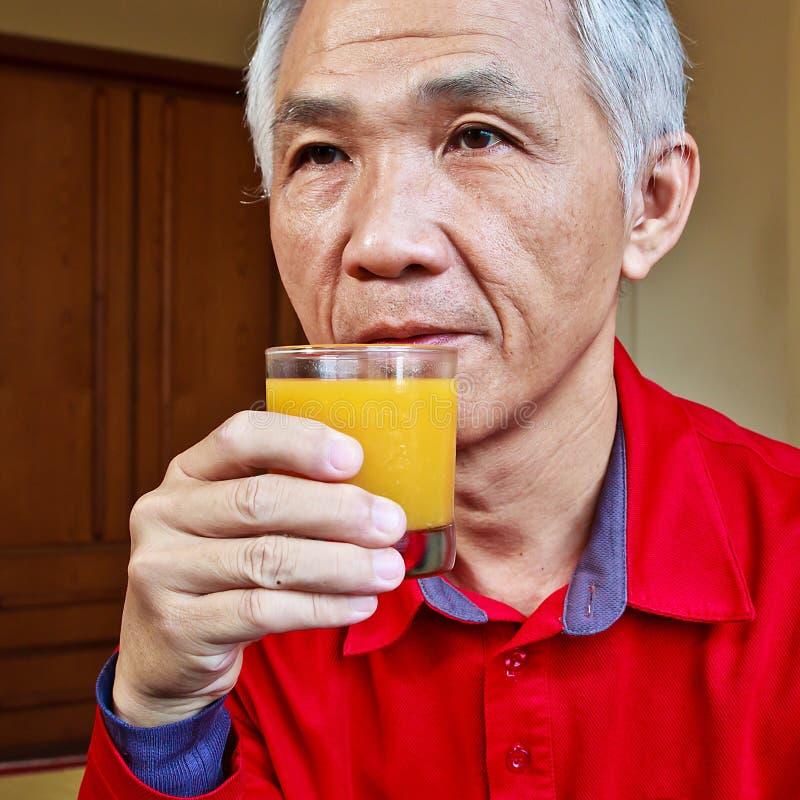 Man who drinking Orange juice royalty free stock photos